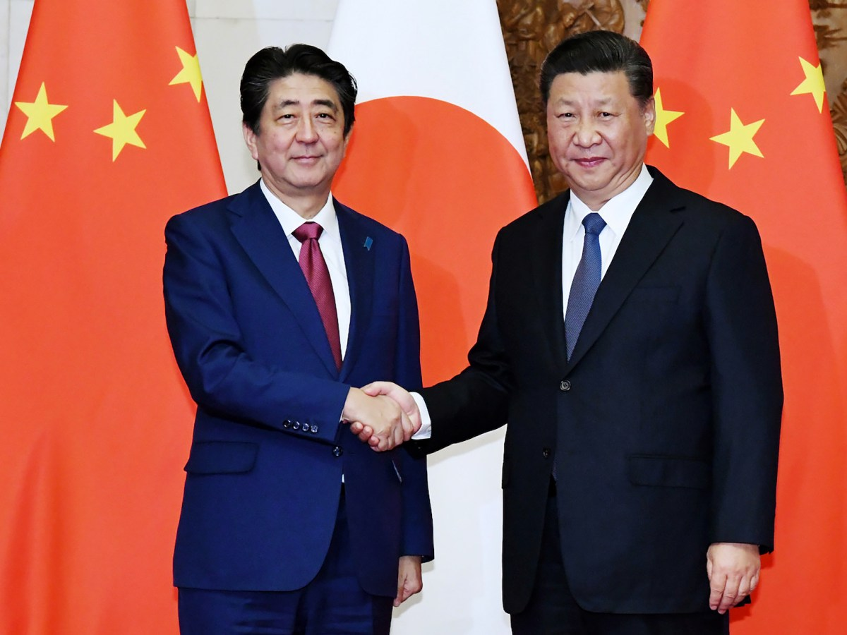 Japan's Prime Minister Shinzo Abe, left, shakes hands with China's President Xi Jinping during their meeting in Beijing on October 26, 2018. Photo: pool via Jiji Press / AFP