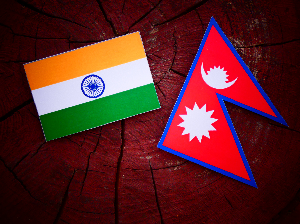 Indian flag with Nepali flag on a tree stump isolated. Image: iStock