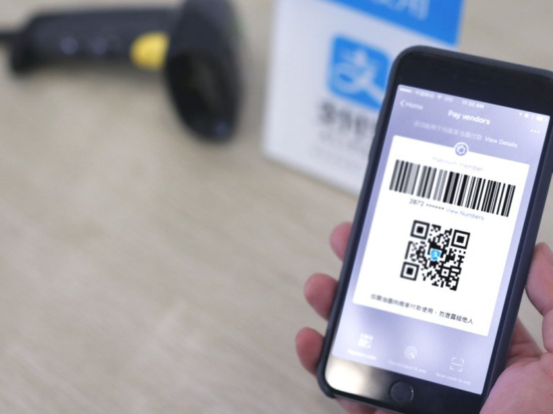 An iPhone user shows the Alipay QR code to make a purchase. Photo: Handout