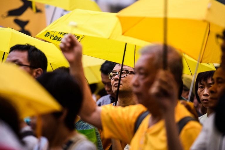 Activists hold yellow umbrellas during a gathering to mark the fourth anniversary of mass pro-democracy rallies, known as the Umbrella Movement, in Hong Kong on September 28. Photo: AFP