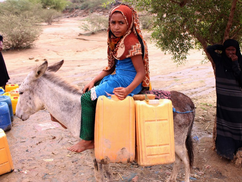 فتاة يمنية مهجرة من مدينة حديدة المطلة على الميناء تركب حمار يحمل حاويات ماء لملئها من بئر في معسكر خارج المدينة في ٢٢ أكتوبر/تشرين الأول ٢٠١٨. صورة: ESSA AHMED/AFP