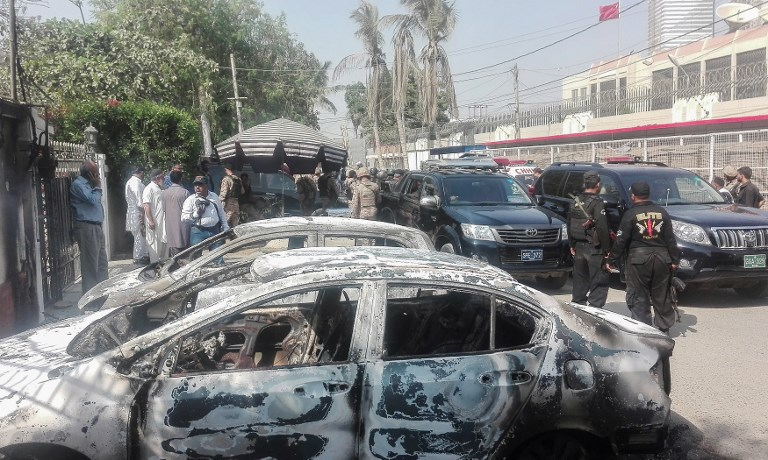 Pakistani security guards stand next to burnt-out cars in front of the Chinese consulate after an attack in Karachi on November 23.  At least two police were killed when three gunmen tried to storm the consulate. All were killed by guards. Photo: AFP / Asif Hassan