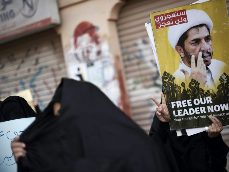 Bahraini protestors hold placards depicting portraits of Sheikh Ali Salman, head of the Shiite opposition movement al-Wefaq, during clashes with riot police following a protest against Salman's arrest in the village of Sitra. Photo: AFP