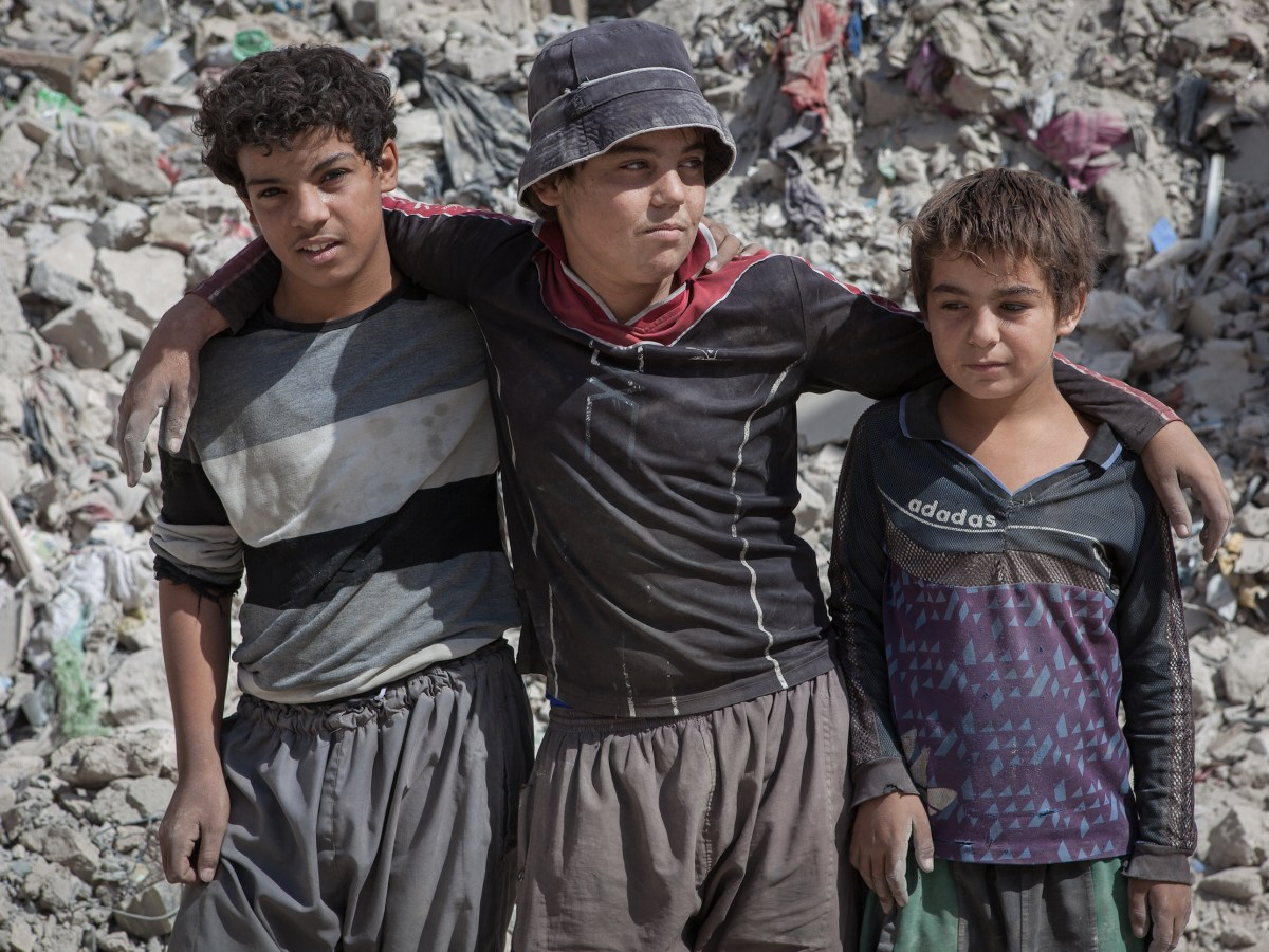 Mohammed Mahmoud Alawi, 15 (center), who has worked as a rag-picker in West Mosul since 2017, with his two younger brothers. They collect metallic and plastic objects to sell. Photo: Sebastian Castelier