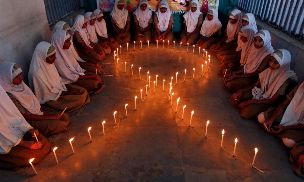 2016年11月30日,在世界愛滋病日前夕,認知HIV/AIDS的活動期間,印度阿美達巴德(Ahmedabad)的女學生們點起排成絲帶形的蠟燭。相片:Reuters / Amit Dave