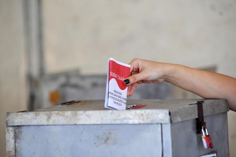 An Indonesian voter casts her vote at a gubernatorial polling station in Jakarta on February 15, 2017. Photo: AFP via Anadolu Agency/Jefri Tarigan