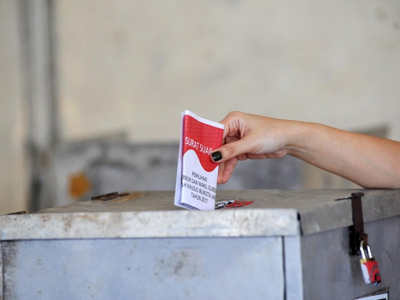 An Indonesian voter casts her vote at a gubernatorial polling station in Jakarta on February 15, 2017. Photo: AFP via Anadolu Agency/Jefri Tarigan