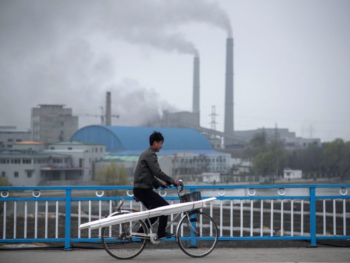A man cycles over a bridge as chimneys of a old power station belch smoke in the background in Pyongyang on April 8, 2017. Photo: AFP/Ed Jones
