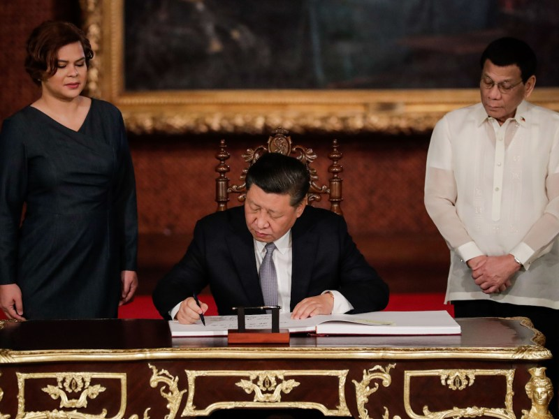 Chinese President Xi Jinping (center) signs the guestbook as Philippines President Rodrigo Duterte (right) and his daughter Sarah Duterte look on at the Malacanang Presidential Palace in Manila on November 20, 2018. Photo: AFP/Mark R Cristino