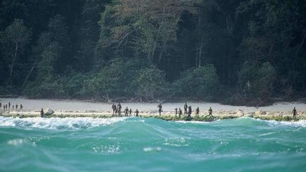 The Sentinelese stand guard on their island's beach. Most contact with the tribe has been made from boats sitting just outside arrow range. Photo: Christian Caron / Creative Commons