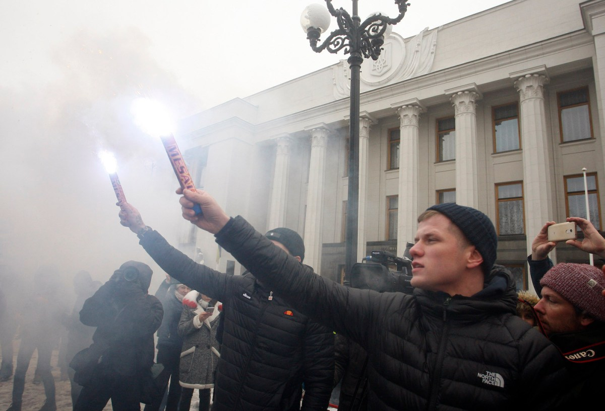 Ukrainian nationalists hold flares during a rally outside parliament on Monday to demand that Kiev break its agreement with Russia on cooperation in the use of the Sea of Azov and the Kerch Strait and impose martial law in the country. The previous day Russia seized three Ukrainian naval ships by force in a strait near Moscow-annexed Crimea. Photo: AFP/ STR / NurPhoto