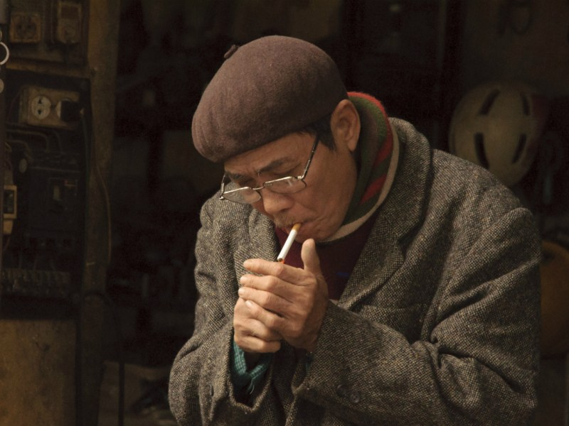 A Vietnamese man lights a cigarette. Photo: iStock