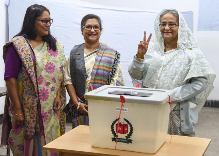 Bangladeshi Prime Minister Sheikh Hasina (R) flashes the victory symbol after casting her vote at a polling station in Dhaka on Sunday. Photo: AFP
