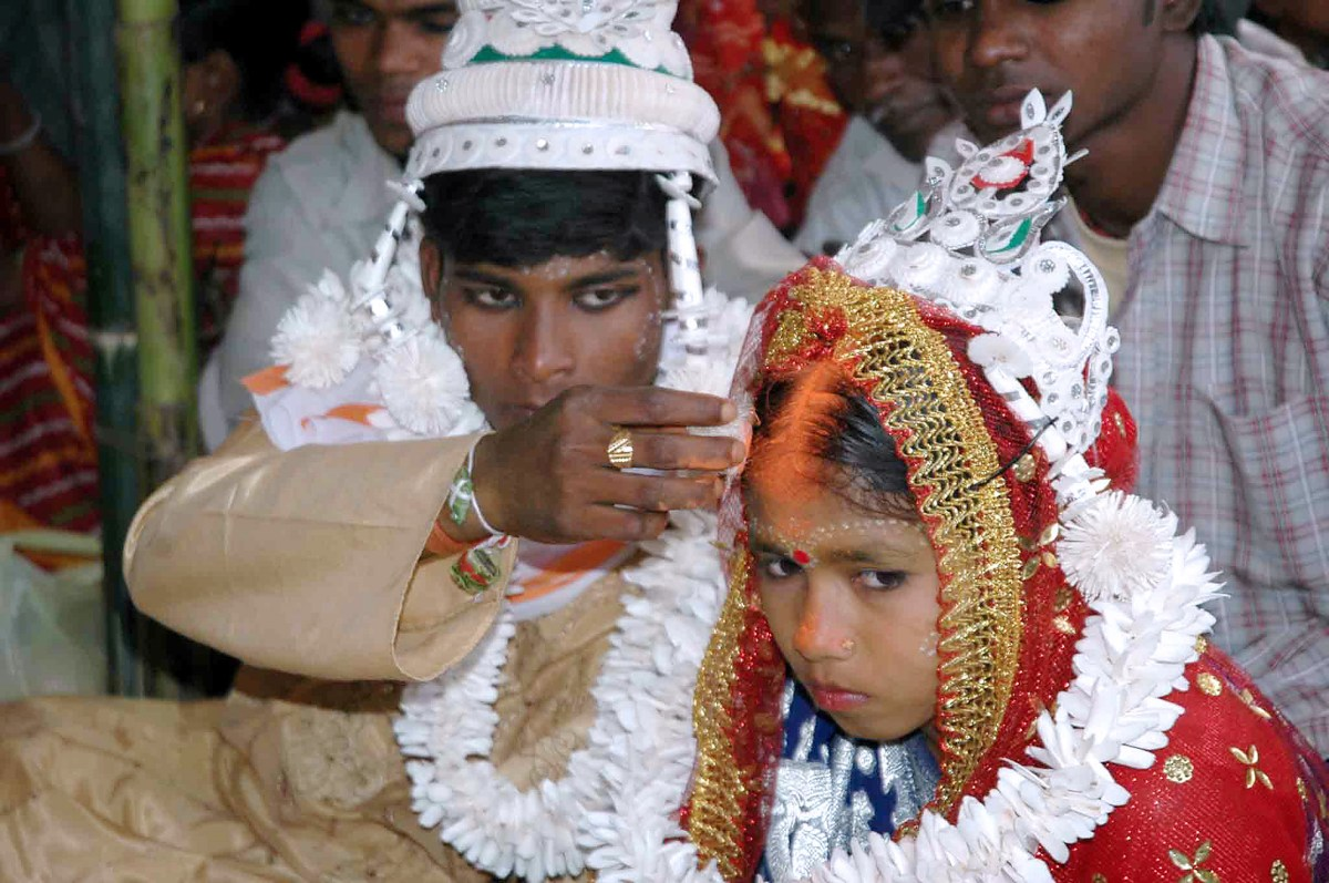 An Indian groom puts vermilion, considered the holy mark of Hindu marriage, on the forehead of his underage bride during a mass marriage program. Photo: AFP / Stroel