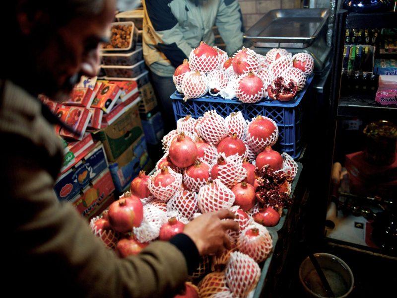 رجل إيراني يقوم بتنظيم الرمان في متجره في وسط طهران في 21 ديسمبر/كانون الأول 2013، استعداداً لاحتفال «يلدا» السنوي، وهو تقليد زرادشتي قديم يعقد في أطول ليلة في العام. لا زال أغلبية الإيرانيين يحتفلون باليوم، إلا أن الكثير يجدون صعوبة في شراء الفاكهة والبضائع الأخرى التي تستخدم تقليدياً في هذا اليوم المميز. صورة: AFP/Behrouz Mehr