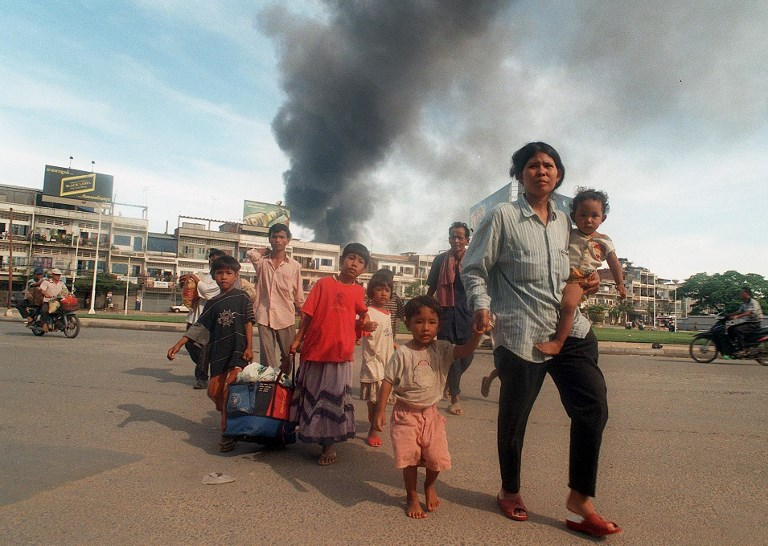 In this 1997 file photo, a family flees Phnom Penh, the Cambodian capital, during heavy factional fighting. The war-ravaged Southeast Asian country produced a steady stream of refugees over decades of conflict. Many displaced people have sought refuge in the United States. Photo: AFP