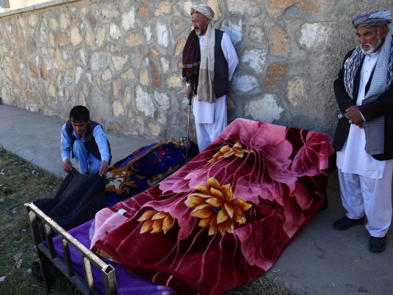Afghan men stand over bodies at the site of an attack by Taliban militants on a government compound in the Khwaja Omari district in the southeast province of Ghazni in April 2018. At least seven people were killed including the local governor, officials said. Photo: Zakeria Hashimi / AFP