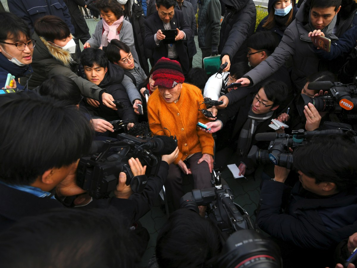 Kim Sung-joo, a victim of forced labor by Japan during its colonial rule of the Korean peninsula, is surrounded by media as she arrives at the Supreme Court in Seoul on November 29. It ordered a Japanese industrial giant to pay compensation over forced wartime labor, the latest decision to strain bilateral ties. Photo: Jung Yeon-je / AFP