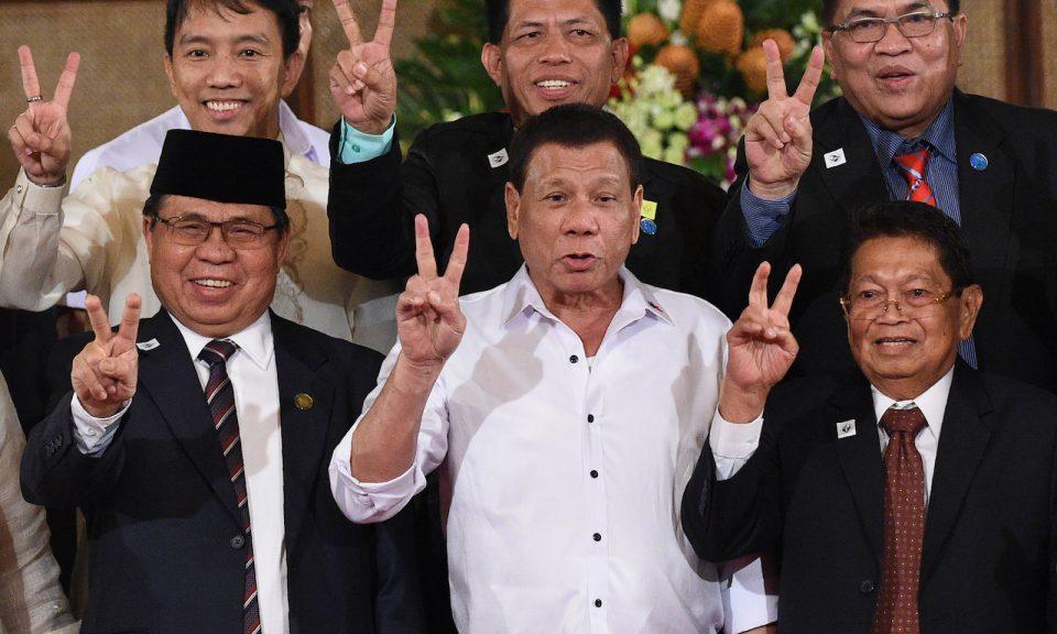 2017年7月17日,MILF主席Al-Hajj Murad、菲律賓總統杜特爾特和MILF副主席雅法(Ghazali Jaafar)在馬尼拉馬拉坎南宮向總統提交的BOL組織法草案儀式上做出代表和平的手勢。相片:AFP / Ted Aljibe