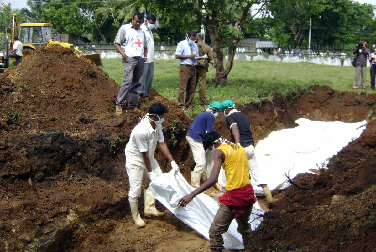 Sri Lankan workers bury the bodies of 41 suspected Tamil Tiger combatants recovered by government forces after heavy fighting in the island's north in January 2009, in Vavuniya. The country's political crisis has cast a cloud over efforts to reveal what happened to thousands of people who disappeared during the civil war. Photo: AFP / STR / aj