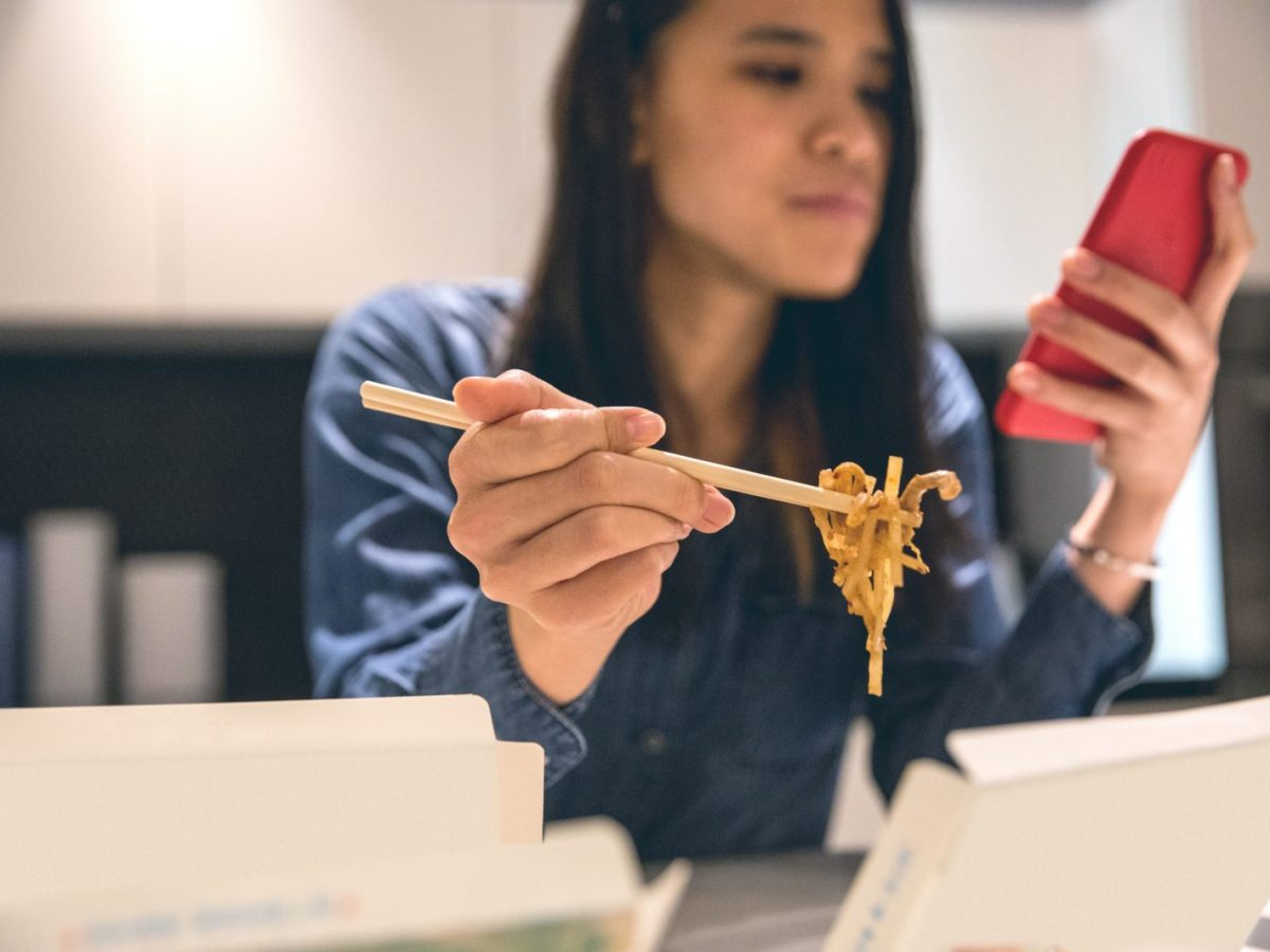 A woman eats food ordered online at her home. Photo: iStock