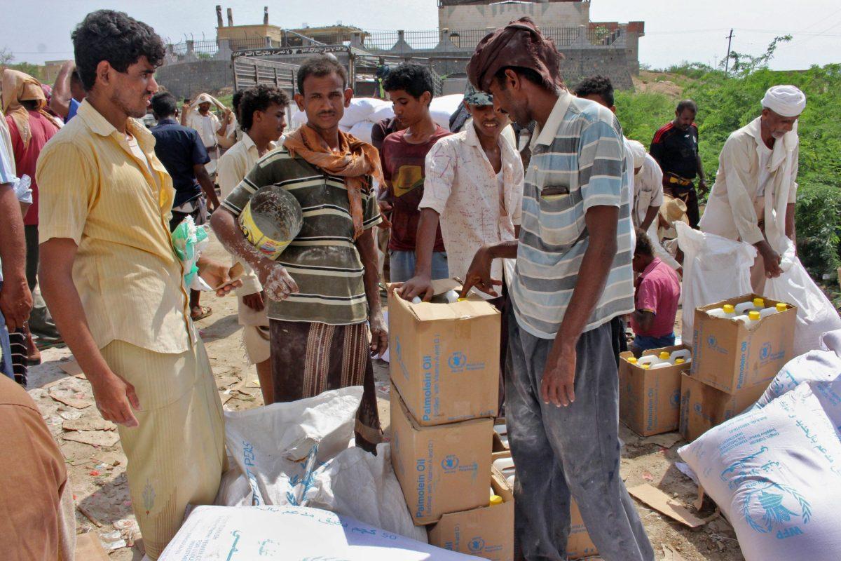 يمنيون مهجرون من مدينة الحديدة يتلقون الدعم الغذائي من برنامج الأغذية العالمي في مدينة حجة الشمالية في 25 سبتمبر/أيلول 2018. صورة: ESSA AHMED / AFP