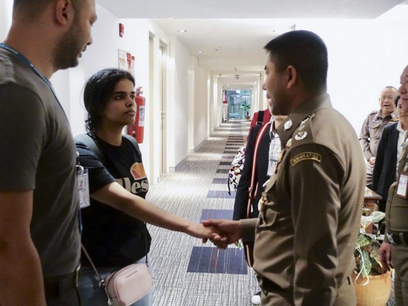 رهف محمد القنون البالغة من العمر 18 عام تصافح ضابط هجرة تايلاندي بمطار بانكوك. صورة: مكتب الهجرة التايلاندي/AFP