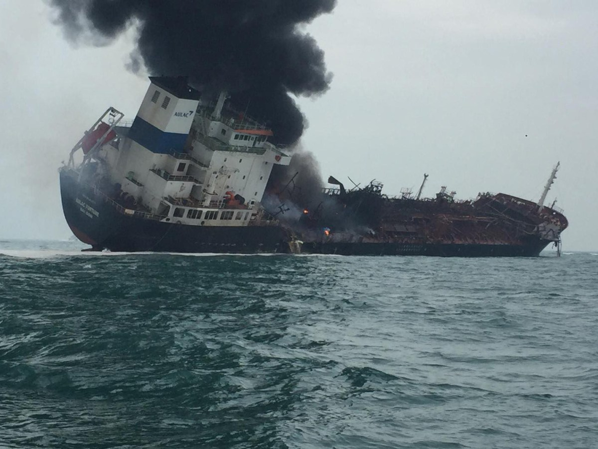 A photo from Hong Kong Police shows smoke rising from an oil tanker tilting to one side in the waters near Hong Kong. At least one person died during the blaze on January 8. Photo: AFP / HK Police handout