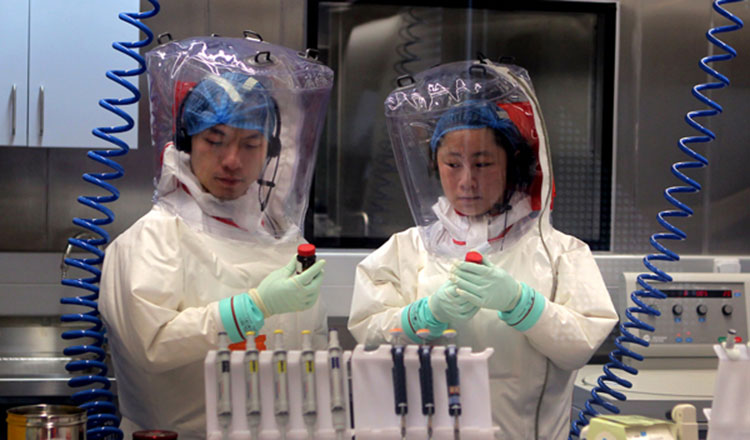 Researchers wearing protective gear work in a level-4 lab. Photo: Xinhua