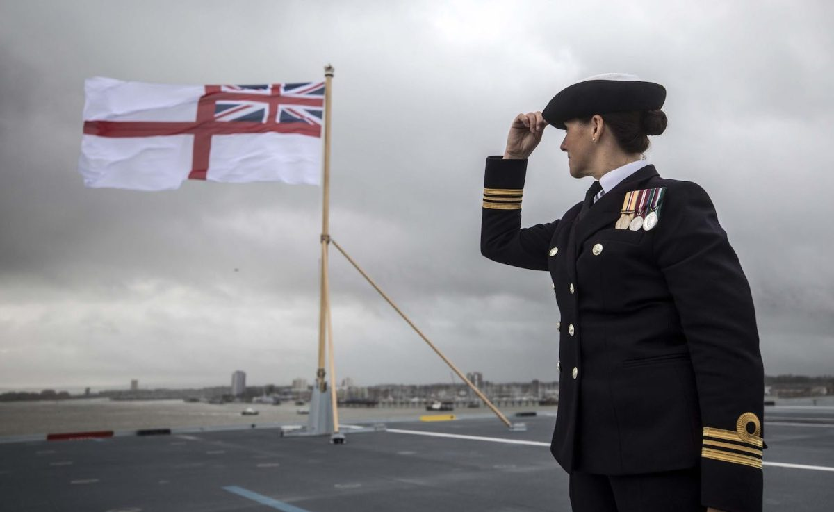 A British naval officer looks up at the fluttering White ensign flag hoisted at the stern during the Commissioning Ceremony for the Royal Navy aircraft carrier HMS Queen Elizabeth at HM Naval Base in Portsmouth, southern England on December 7, 2017. Photo: AFP/Richard Pohle