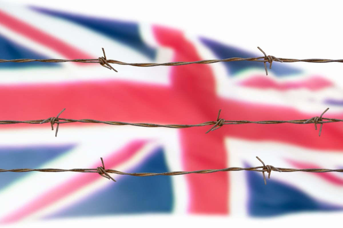 Metal fence with barbed wire on a Britain flag. Separation concept, borders protection.Social issues on refugees or illegal immigrants. image istock