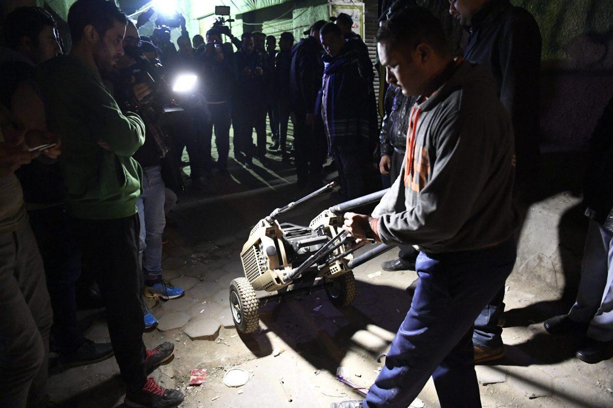 شرطي مصري في ثياب ملكية يدخل أحد المعدات إلى مكان جثمان الانتحاري الذي فجر نفسه بالقرب من الجامع اﻷزهر بالقاهرة في 19 فبراير/شباط 2019. صورة: Khaled DESOUKI / AFP