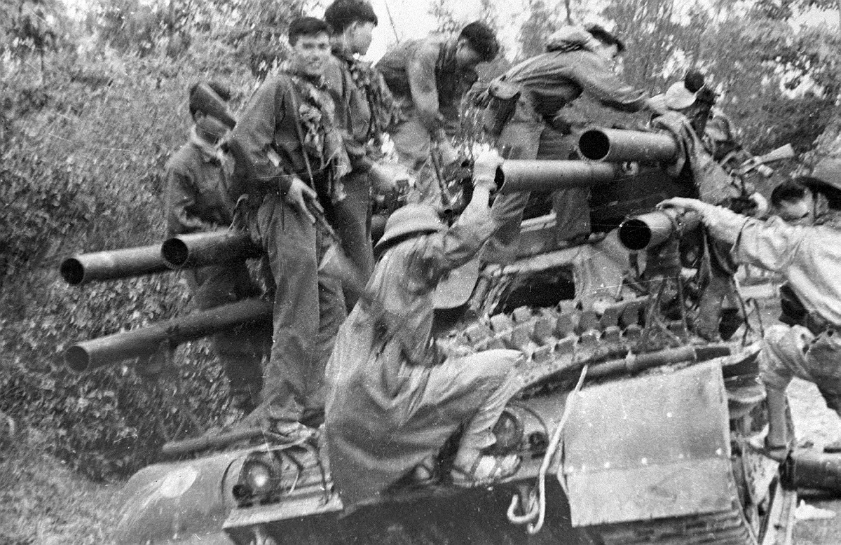 Vietcong soldiers climb on to an abandoned US tank in Hue in 1968 during the Tet offensive. Photo: VNA / AFP