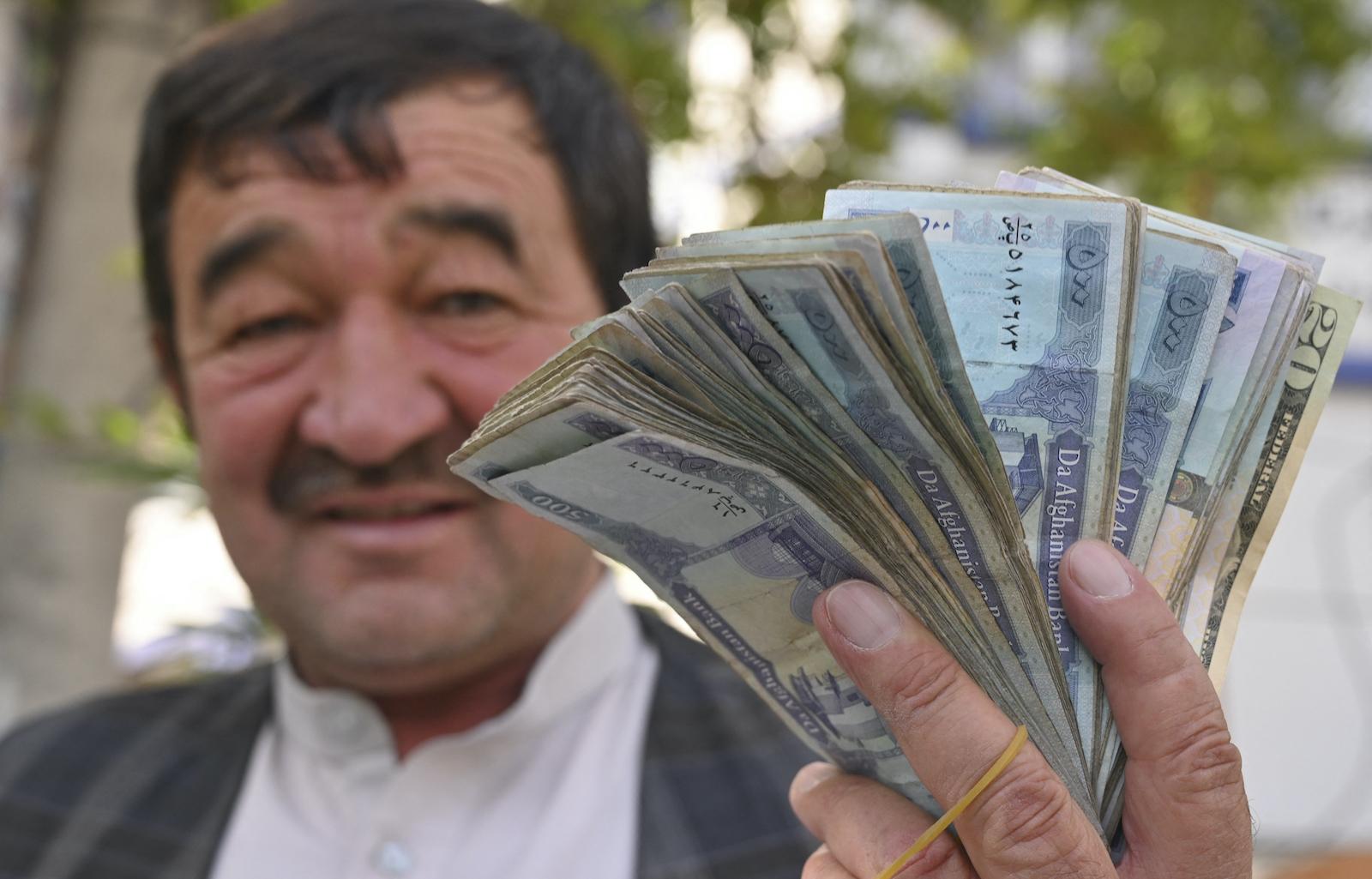30 年 2021 月 XNUMX 日,一名货币兑换商在喀布尔的一条街道上展示阿富汗阿富汗尼钞票。照片:AFP/Adel Berry