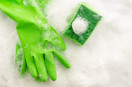 Top view of protective green gloves and sponge on soapy background. Housework concept. Copy space, top view