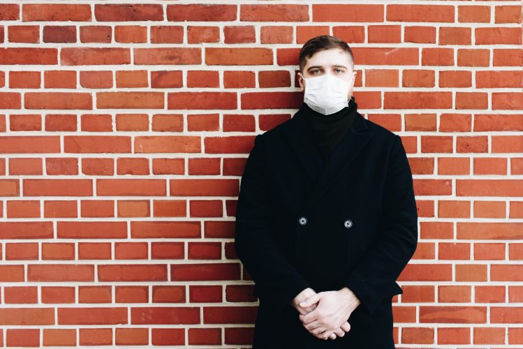 Young caucasian man wearing a surgical mask to protect from coronavirus covid-19 during global pandemic standing against a wall