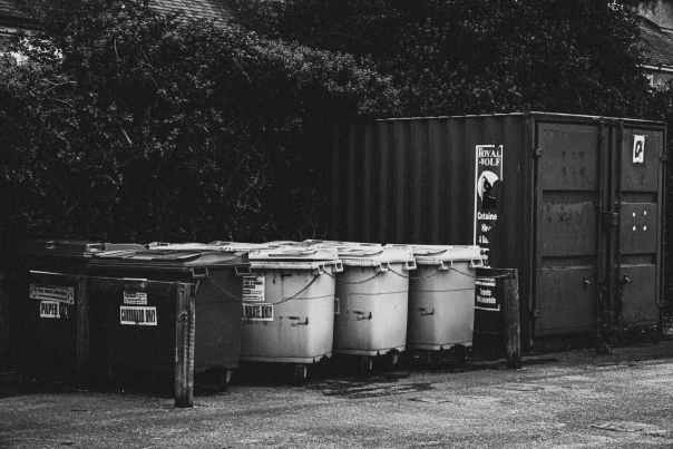 grayscale photography of trash bins