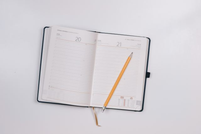 Open diary on a desk with a yellow pencil