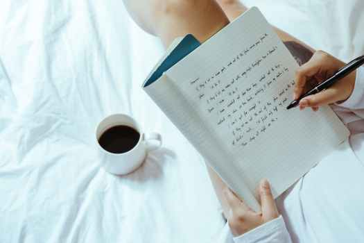 crop woman with coffee writing in notebook on bed