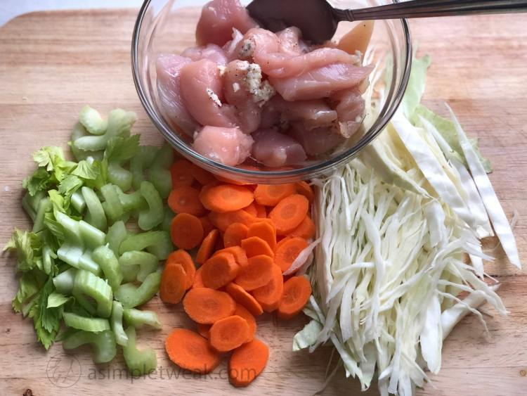 a bowl of chicken tenderloin, diced carrots, celery and cabbage