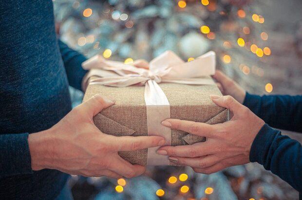 Muška i ženska ruka na upakovanom poklonu sa roze mašnom