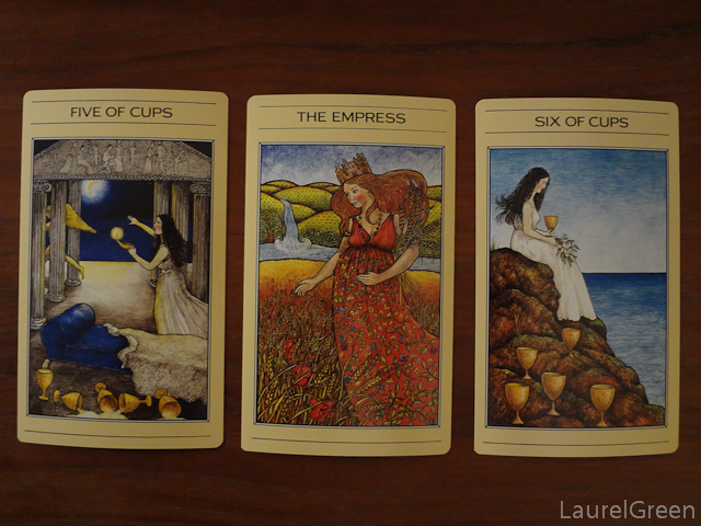 a three card tarot spread with the five of cups, the empress and the six of cups