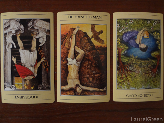a three card tarot spread with judgement reversed, the hanged man and the page of cups reversed