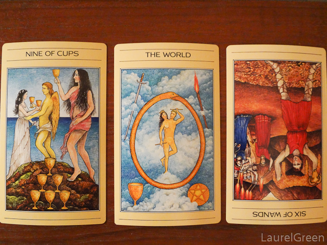 a three card tarot spread with the nine of cups, the world and the six of wands reversed