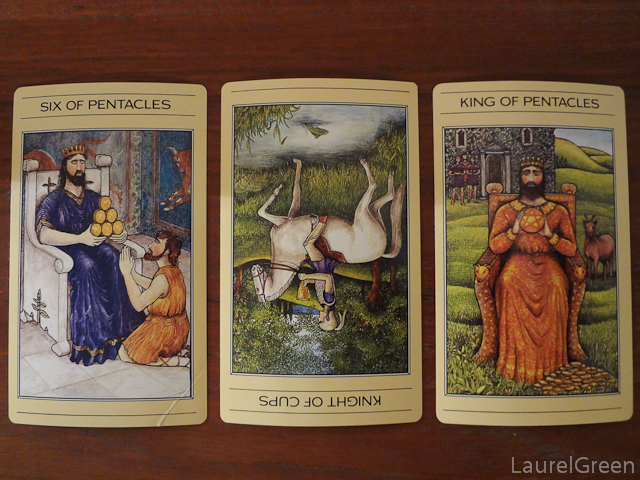 a three card tarot spread with the six of pentacles, the knight of cups reversed and the king of pentacles