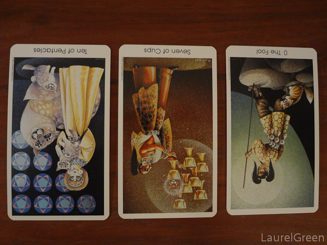 a three card tarot spread with the ten of pentacles reversed, the seven of cups reversed and the fool reversed