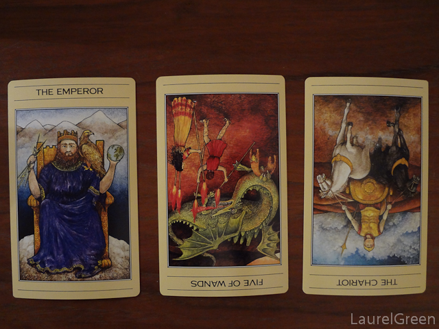 a three card tarot spread with the emperor, the five of wands reversed and the chariot reversed