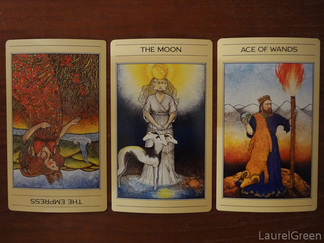 a three card tarot spread with the empress reversed, the moon and the ace of wands