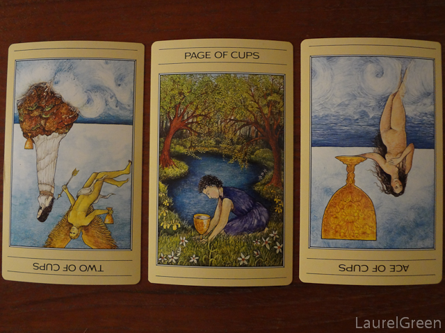 a three card tarot spread with the two of cups reversed, the page of cups and the ace of cups reversed