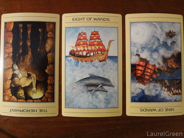 a three card tarot spread with the hierophant reversed, the eight of wands and the nine of wands reversed